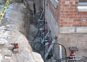 Foundation push piers installed around a house with a foundation settlement issues in East Greenbush