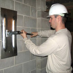 installing a wall anchor to repair an bowing foundation wall in Latham