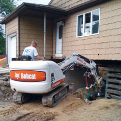 Excavating to expose the foundation walls and footings for a replacement job in Hudson