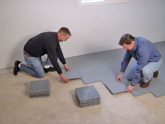 ... Contractors Installing Basement Sub Floor Tiles And Matting On A  Concrete Basement Floor In Amsterdam,